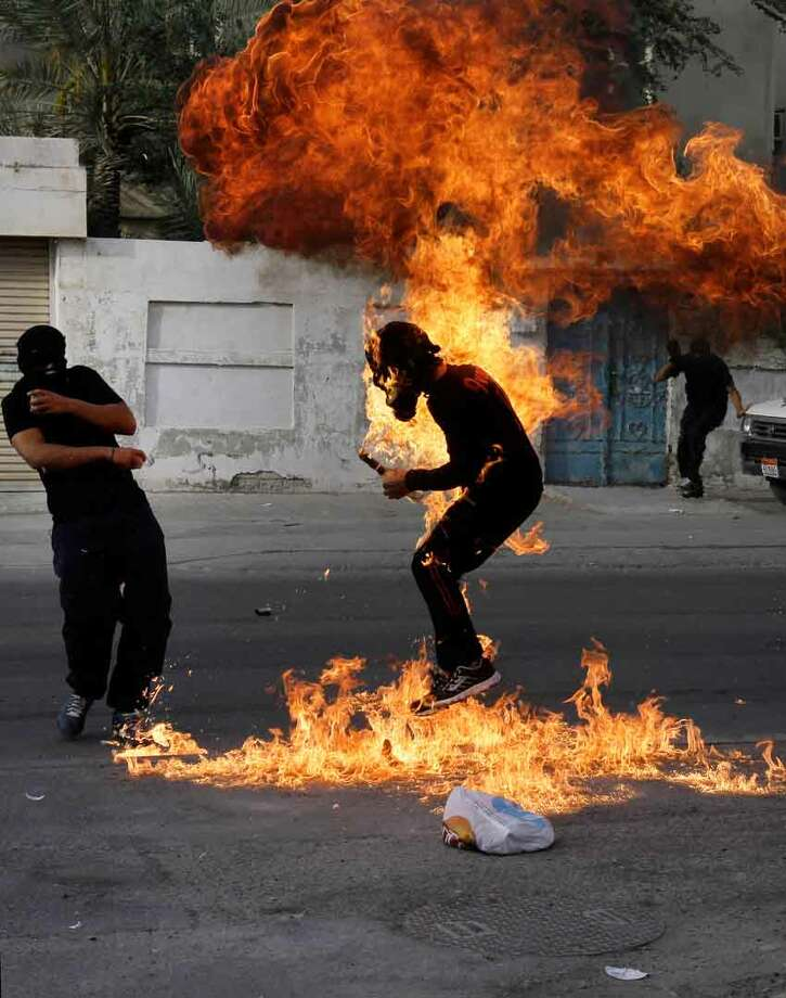 "A Bahraini anti-government protester is engulfed in flames when a shot fired by riot police hit the petrol bomb in his hand that he was preparing to throw during clashes in Sanabis, Bahrain, Thursday, March 14, 2013. Protests and clashes erupted in opposition areas nationwide Thursday with government opponents observing a ""Dignity Strike"" _ blocking roads, closing shops, protesting and staying home from work and school _ called by the more radical February 14 youth group. (AP Photo/Hasan Jamali) Photo: ASSOCIATED PRESS / AP2013"