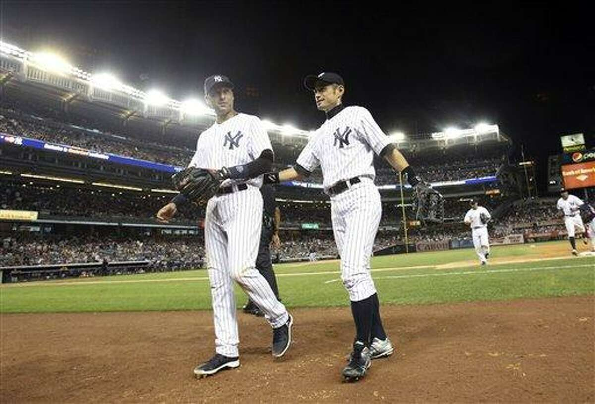 New York Yankees' Ichiro Suzuki, right, and Derek Jeter leave the field during the eighth inning of a baseball game against the Boston Red Sox at Yankee Stadium in New York, Friday, July 27, 2012. The Yankees defeated the Red Sox 10-3. (AP Photo/Seth Wenig)