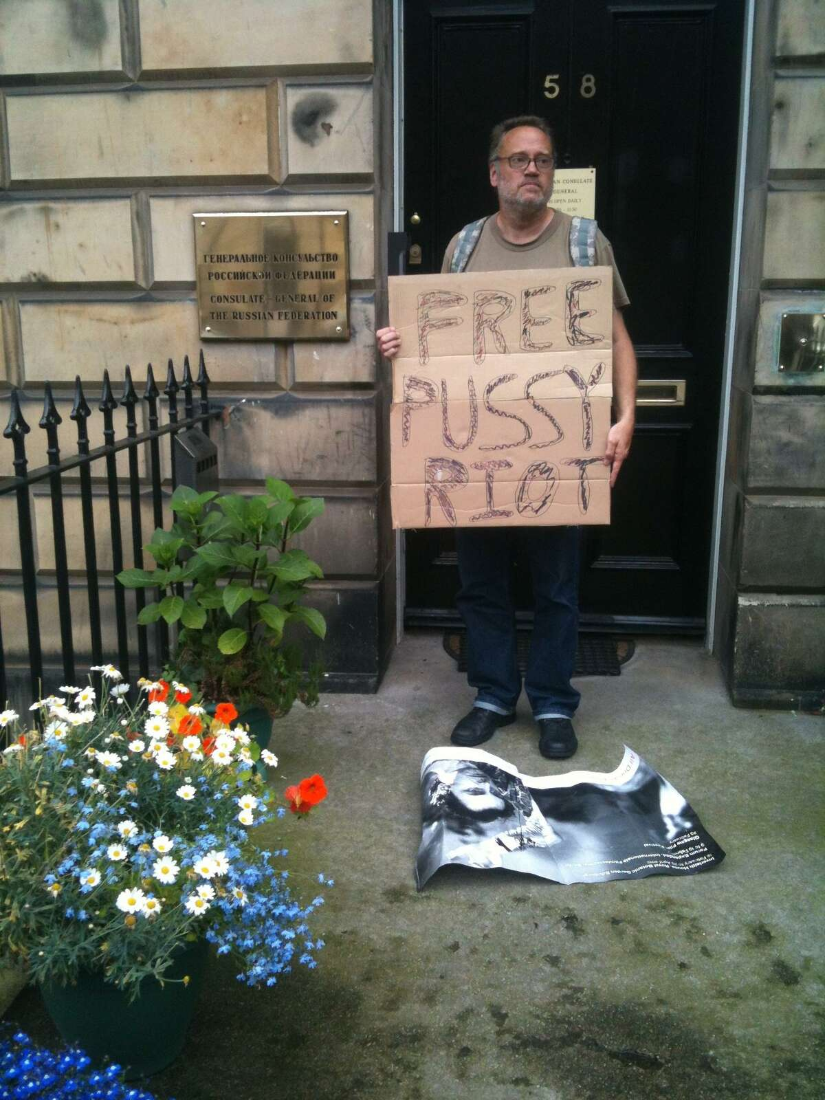 Ray Neal, a member of Occupy New Haven, stands in front of the Russian Consulate in Edinburgh, Scotland, with a sign protesting the arrest and conviction of some members of the Russian punk band, Pussy Riot. Contributed photo