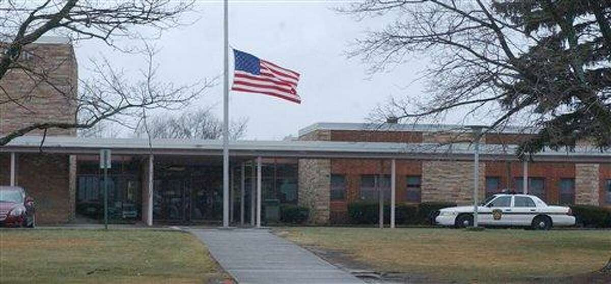 The American flag flies at half-staff Friday, Dec. 21, 2012, as state police go on protective patrol at the Hazleton Ninth Grade Center, in Hazleton Pa., one week after the mass shootings at Sandy Hook Elementary School in Newtown, Conn. (AP Photo/Hazleton Standard-Speaker, Eric Conover)