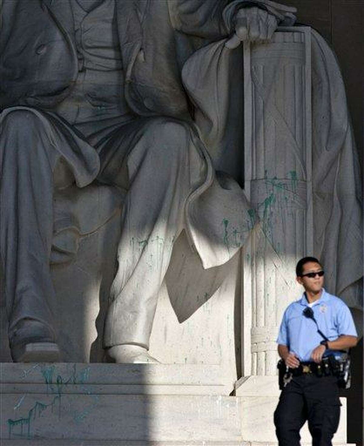 A U.S. Park Police officer stands guard next to the statue of Abraham Lincoln at the memorial in Washington, Friday, July 26, 2013, after the memorial was closed to visitors after someone splattered green paint on the statue and the floor area. Police say the apparent vandalism was discovered early Friday morning. No words, letters or symbols were visible in the paint. (AP Photo/J. Scott Applewhite)