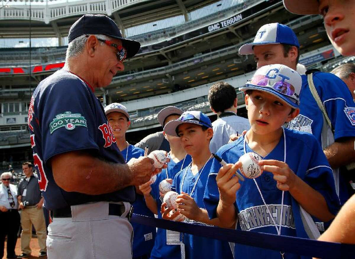 ASSOCIATED PRESS Boston Red Sox manager Bobby Valentine (25) signs autographs for members of the Connecticut Little League 10-year-old championship team from North Stamford before Saturday's game against the New York Yankees at Yankee Stadium in New York.