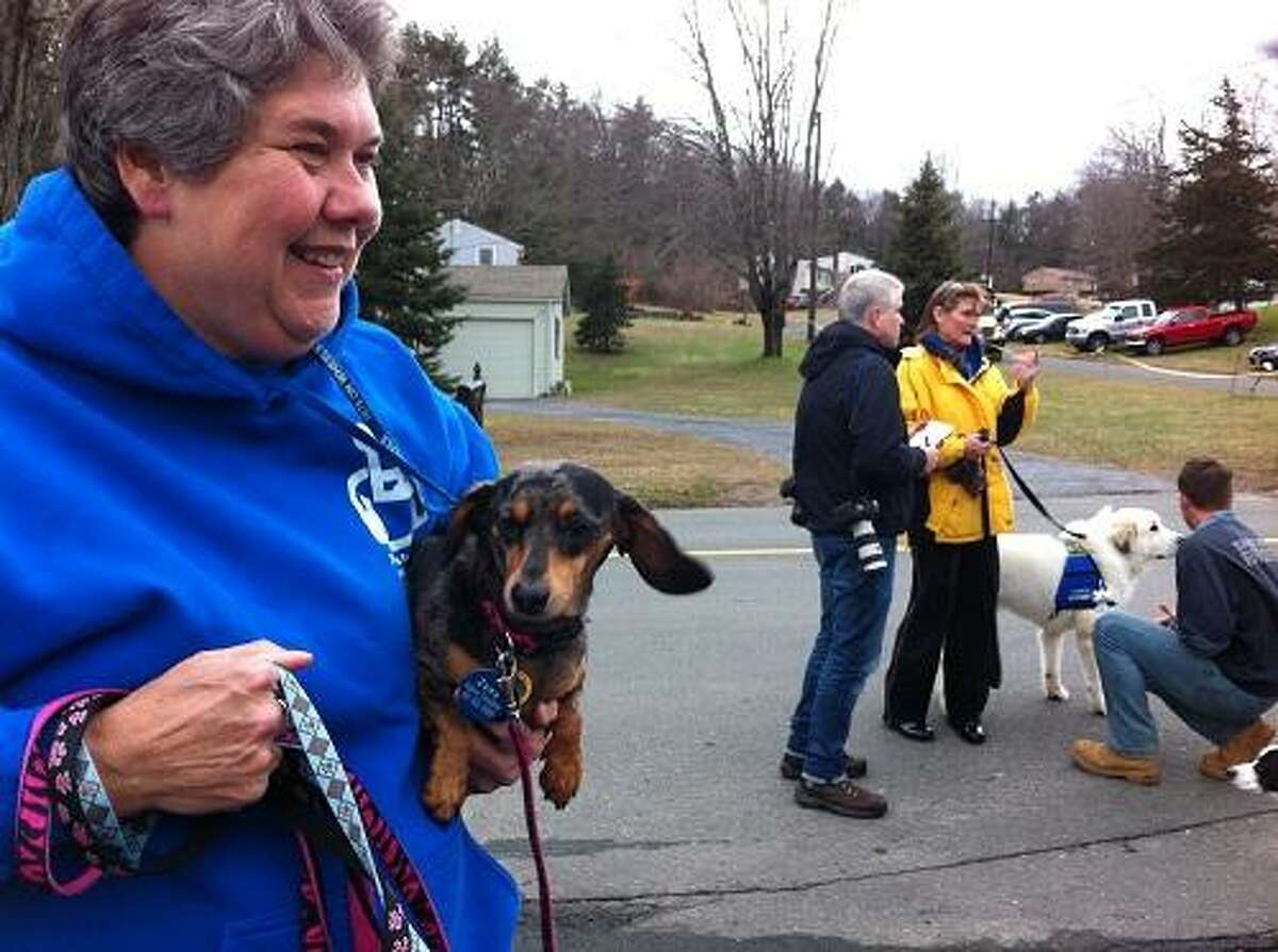 Valerie Donaldson of Baltimore holds Zoey, a miniature dachshund (and the leashes of miniature dachshunds Abby and Jasmine) after they all arrived on the Pets on Wheels bus at the Sandy Hook Volunteer Fire & Rescue firehouse. In the background, another canine member meets a Sandy Hook firefighter. Mark Zaretsky/Register