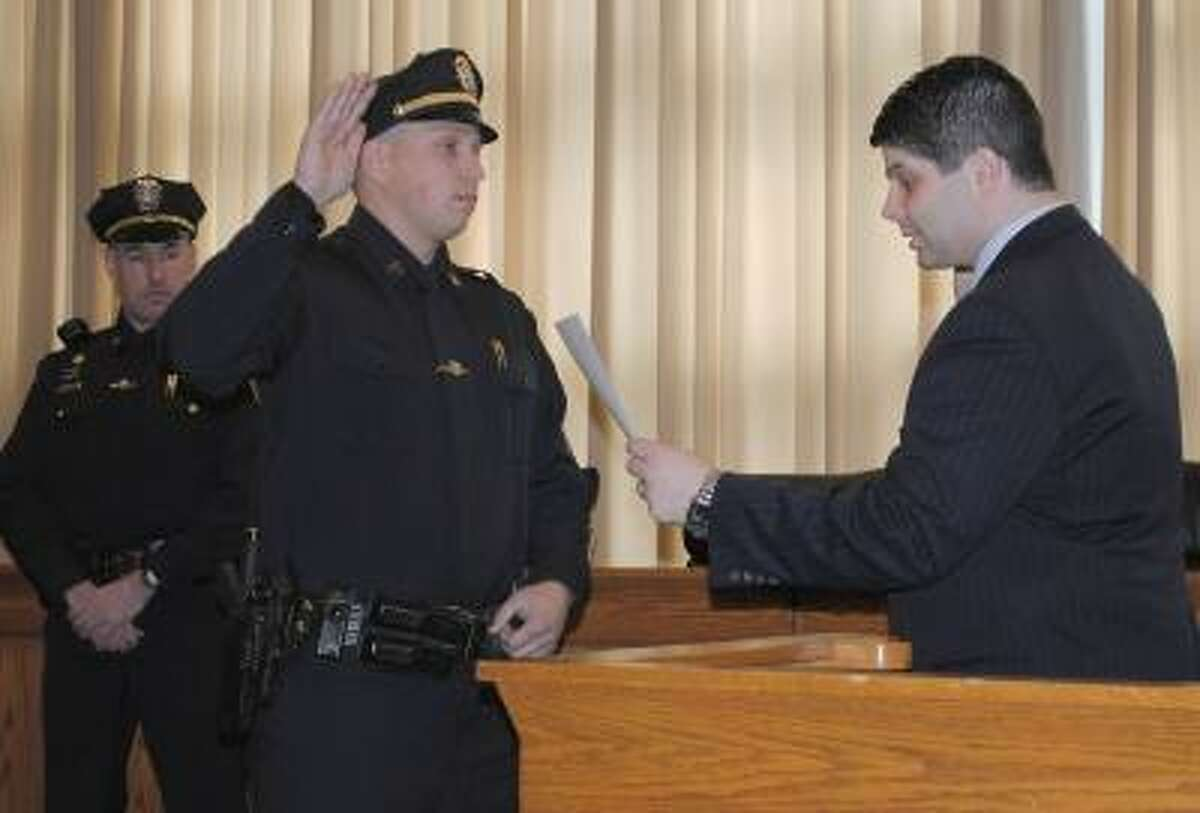 Viktoria Sundqvist/The Middletown Press Middletown Mayor Daniel Drew swears in Daniel Smith to his new sergeant position in a ceremony at Council Chambers Friday.