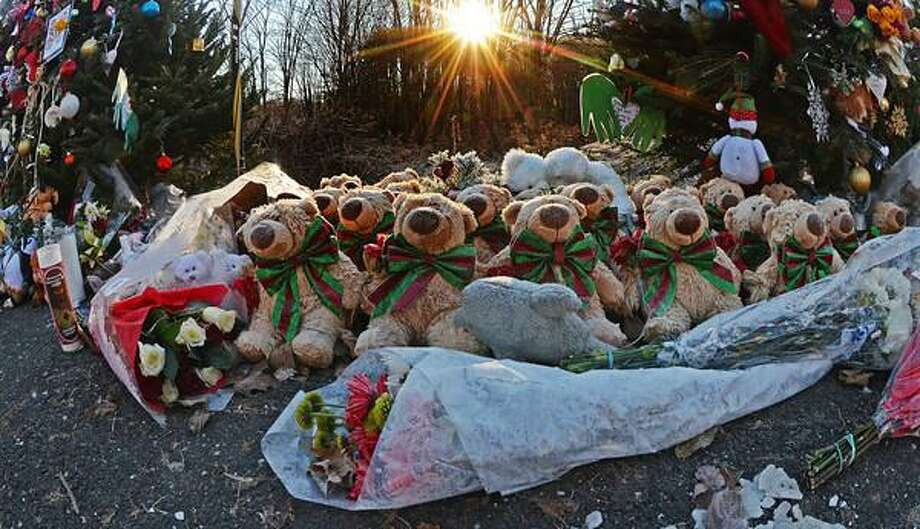 Staff photos by Tom Kelly IV The memorial setup near the Sandy Hook firehouse, and the entrance road to Sandy Hook Elementary School continues to grow as seen here early Thursday morning December 20, 2012. The sun rises above the trees illuminating the fur on these stuffed teddy bears. / © 2012 Tom Kelly IV