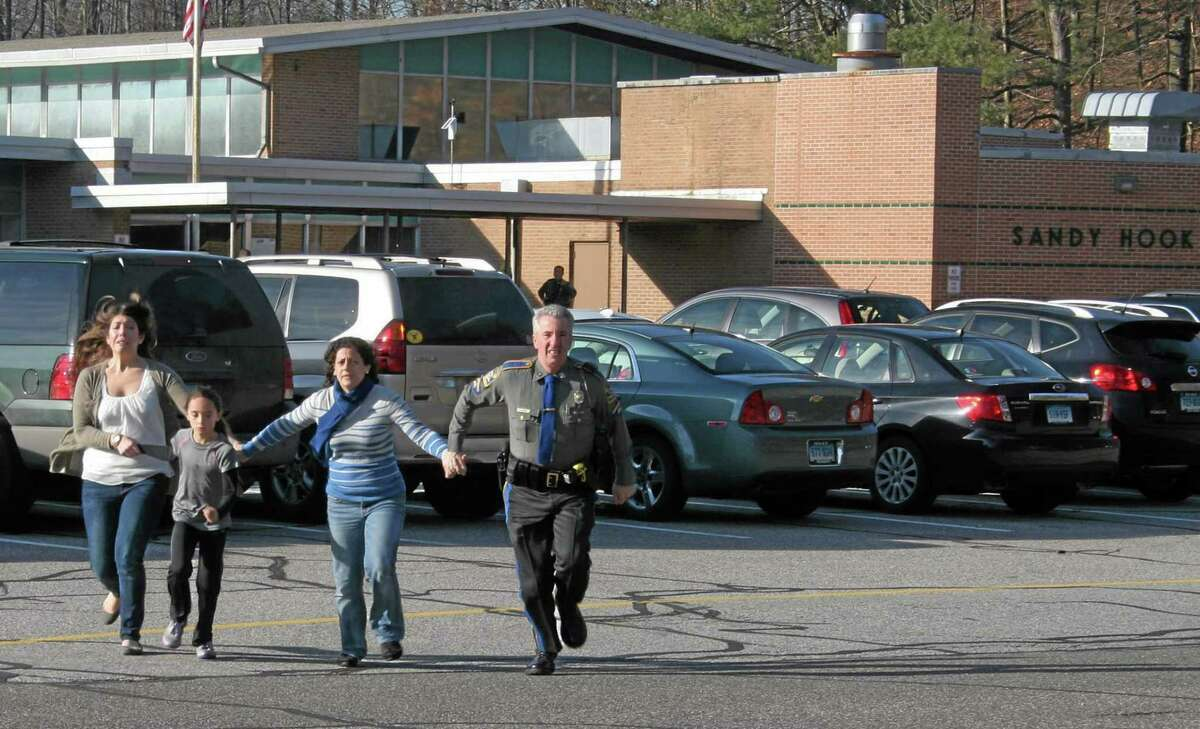 FILE - In this Friday, Dec. 14, 2012, file photo provided by the Newtown Bee, a police officer leads two women and a child from Sandy Hook Elementary School in Newtown, Conn., where a gunman opened fire, killing 26 people, including 20 children. AP Photo/Newtown Bee, Shannon Hicks, File)