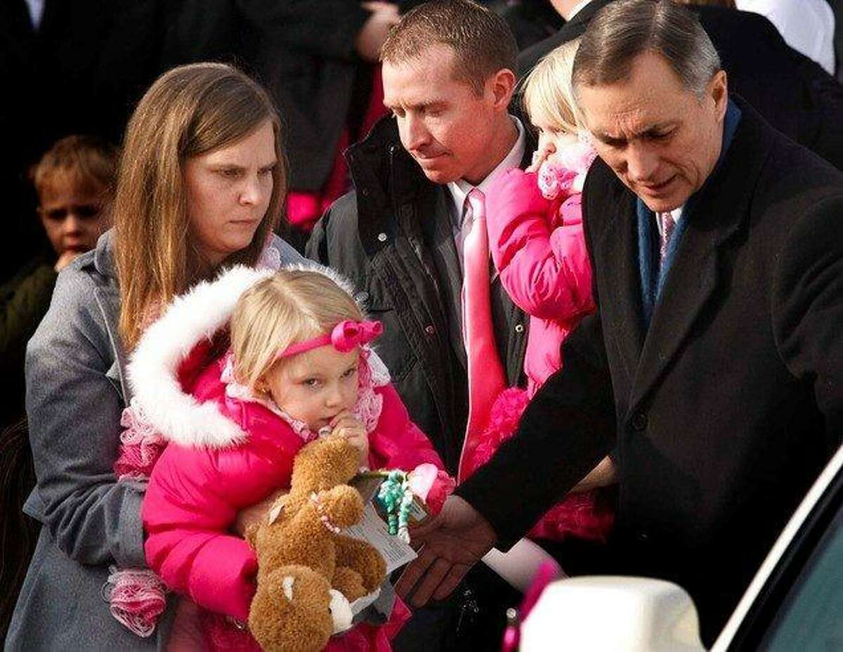Robbie Parker carries daughter Madeline, 4, and Alissa Parker carries Samantha, 2, from the funeral service for their oldest daughter Emilie, Saturday December 22, 2012 in Ogden. Funeral services for Connecticut elementary shooting victim Emilie Parker were held in Ogden at the at the Rock Cliff LDS Stake Center. Emilie, whose family has Ogden roots, was one of 20 children and six adult victims killed in the Dec. 14 mass shooting at Sandy Hook Elementary in Newtown, Conn. The shooting took the lives of 26 people, before the gunman killed himself. Leah Hogsten