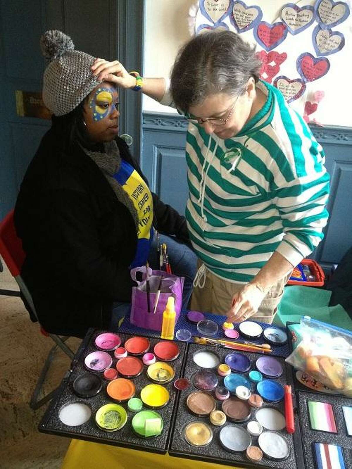 Pictured with painter Robbie Pack is Ericka Taylor of Pittsburgh, Pa. Pack, of Fairfield, Conn., came to Newtown to lift spirits by painting faces. Taylor came to Newtown with a friend to do outreach with Victory Center for Youth, of Cleveland.