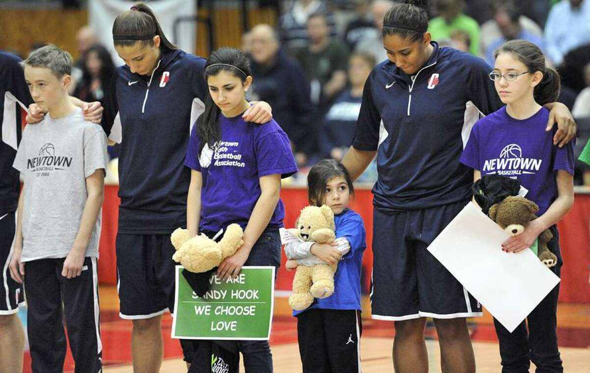 Connecticut's Caroline Doty, second from left, and Kaleena Mosqueda-Lewis, second from right, stands with children from Newtown's Youth Basketball Association during a ceremony for the victims of the Sandy Hook Elementary School shooting before an NCAA women's college basketball game against the University of Hartford, Saturday, Dec. 22, 2012, in West Hartford, Conn. (AP Photo/Jessica Hill)