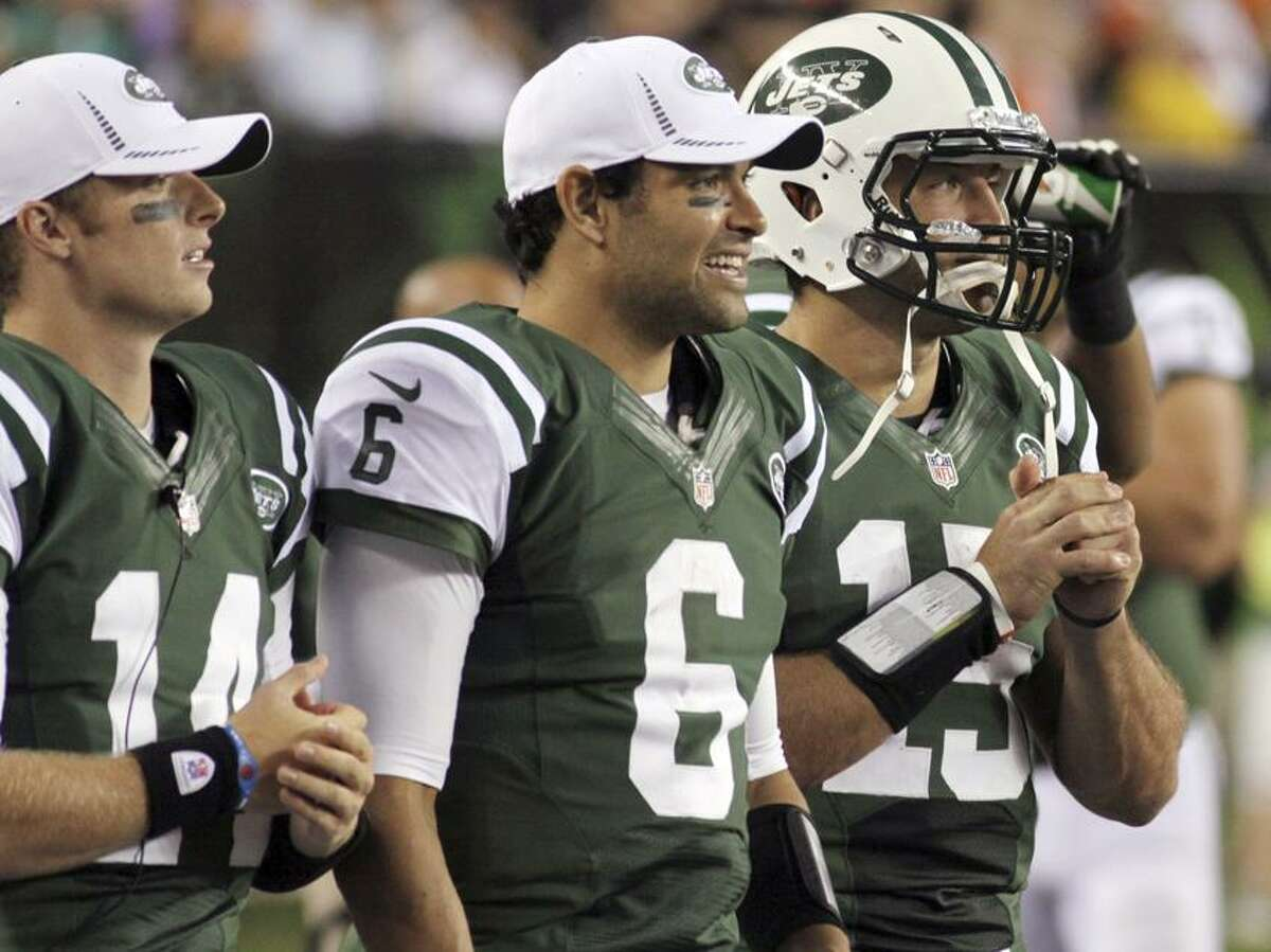 FILE - In this Aug. 10, 2012, file photo, New York Jets quarterbacks, from left, Greg McElroy, Mark Sanchez and Tim Tebow watch from the sidelines during the first half of a preseason NFL football game against the Cincinnati Bengals in Cincinnati. Rex Ryan decided to bench Sanchez on Tuesday, Dec. 18, 2012, in favor of Greg McElroy after the fourth-year quarterback had another miserable performance in a 14-10 loss at Tennessee on Monday night that eliminated New York from playoff contention. While Sanchez blew the second chance Ryan gave him a few weeks ago, Tebow was leapfrogged by a third-stringer, fueling speculation that the team has little confidence in him as a quarterback. (AP Photo/Tom Uhlman, File)