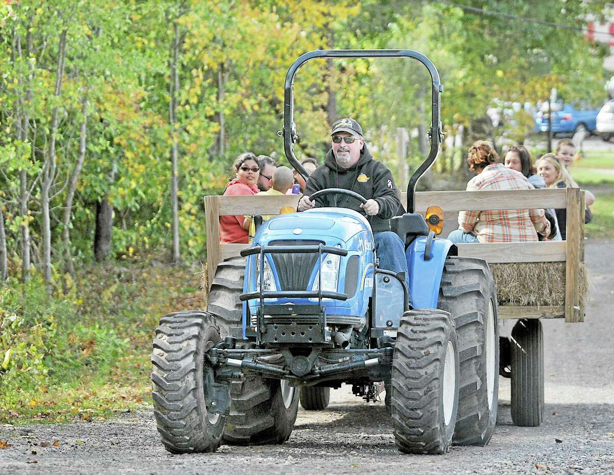 """Kevin MacGranor behind the wheel of a New Holland tractor takes guests visiting Pumpkintown for """"The Ride"""" which consists of a 20 minute loop through their decorated woods. The hayride operates every half hour every day from 10 a.m. to 5 p.m. Catherine Avalone - The Middletown Press"""
