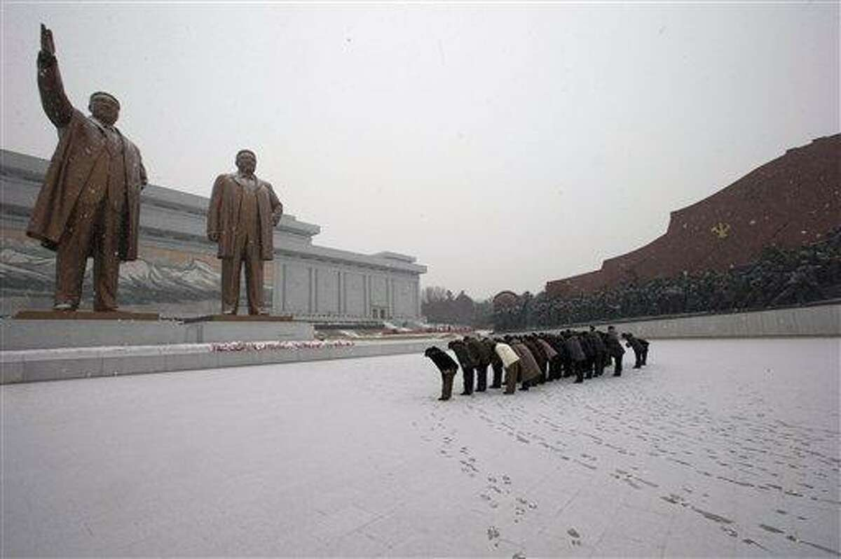 North Koreans bow in front of the statues of late North Korean leaders Kim Il Sung, left, and Kim Jong Il at Mansu Hill as it snows in Pyongyang, North Korea, Friday, Dec. 21, 2012. (AP Photo/Ng Han Guan)