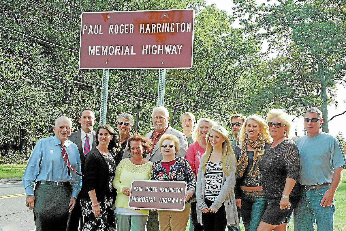 Middlesex Chamber of Commerce President Larry McHugh, state Sen. Paul Doyle and state Rep. Christie Carpino join family and friends of Paul Roger Harrington for the unveiling of a sign naming a portion of Route 3 in Cromwell in his honor.