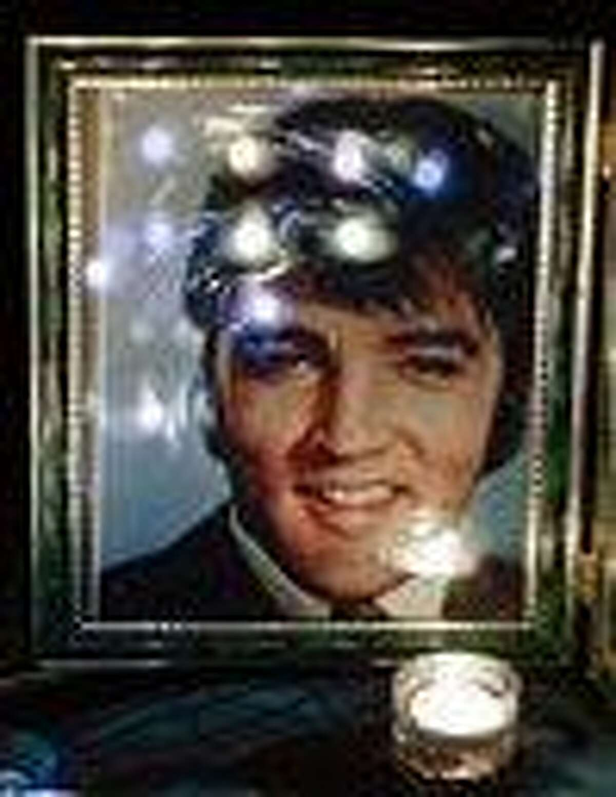 Candles are reflected in a photo of Elvis Presley at a memorial set up by a fan at a candlelight vigil at Graceland, Presley's Memphis, Tenn., home, on Wednesday. Fans from around the world are at Graceland to commemorate the 35th anniversary of Presley's death. (AP Photo/Mark Humphrey)