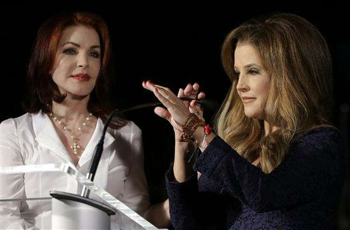 Priscilla Presley, left, Elvis Presley's ex-wife, and Lisa Marie Presley, right, Elvis and Priscilla's daughter, speak to fans gathered at a candlelight vigil at Graceland, Elvis Presley's Memphis, Tenn., home, on Wednesday. Fans from around the world are at Graceland to commemorate the 35th anniversary of Elvis Presley's death. (AP Photo/Mark Humphrey)