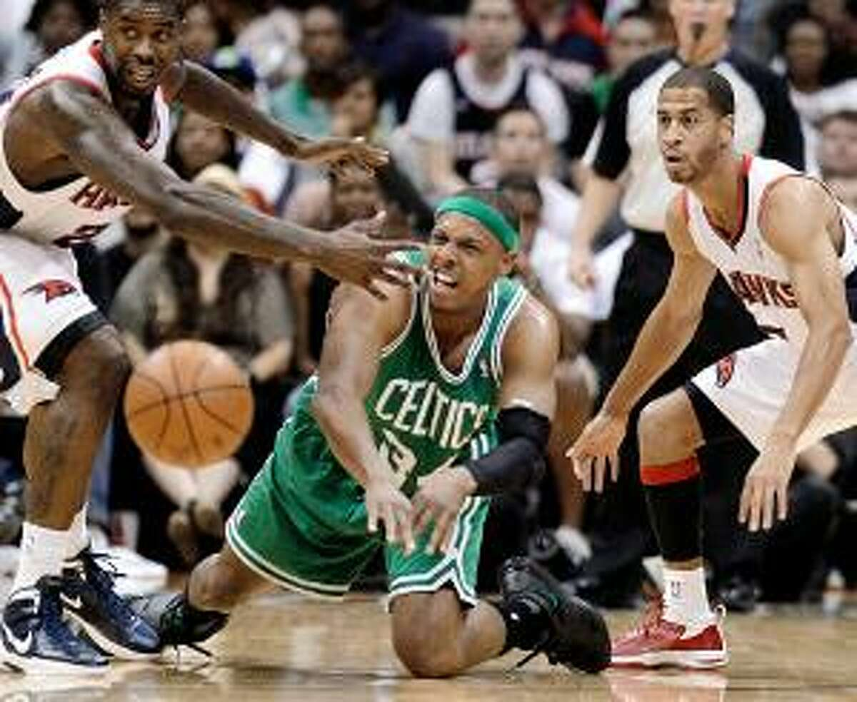 ASSOCIATED PRESS Boston Celtics forward Paul Pierce, center, passes the ball as Atlanta's Marvin Williams, left, and Jannero Pargo defend during the second quarter of Game 1 of their first-round NBA playoff series Sunday in Atlanta. The Hawks won the game 83-74.