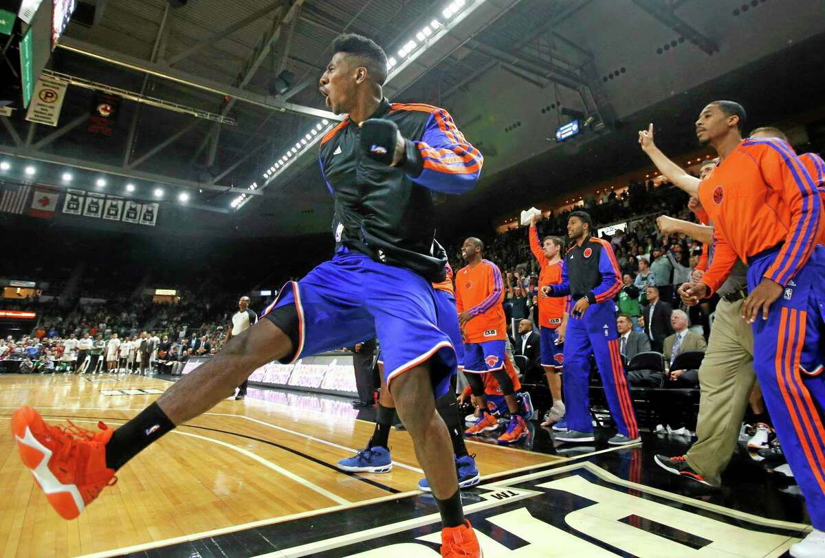 New York Knicks shooting guard Iman Shumpert, left, celebrates along with teammates on the bench as the Knicks defeated the Boston Celtics 103-102 in a preseason NBA game in Providence, R.I., Wednesday.