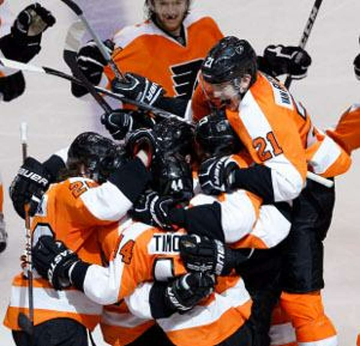 ASSOCIATED PRESS Philadelphia Flyers' James van Riemsdyk (21) jumps on the pile surrounding Danny Briere (48) after Briere's winning goal in the overtime period of Game 1 in a second-round NHL Stanley Cup series with the New Jersey Devils Sunday in Philadelphia. The Flyers won 4-3 in overtime.