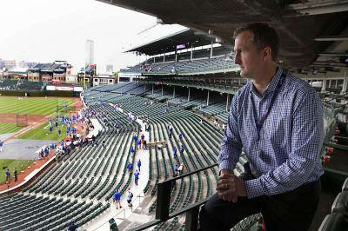 In this May 17, 2013 photo, Crane Kenney, the Chicago Cubs' president of business operations, looks out over Wrigley Field during batting practice before a Cubs baseball game in Chicago.