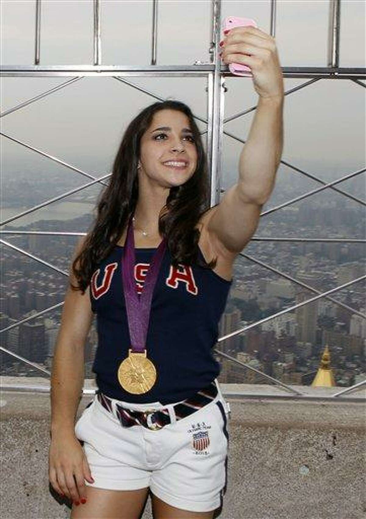 Aly Raisman, of the 2012 US Women's Gymnastics Olympic Team, takes a photo of herself on the observation deck of the Empire State Building earlier this week. She recently returned home to a warm welcome in Massachusetts. Associated Press