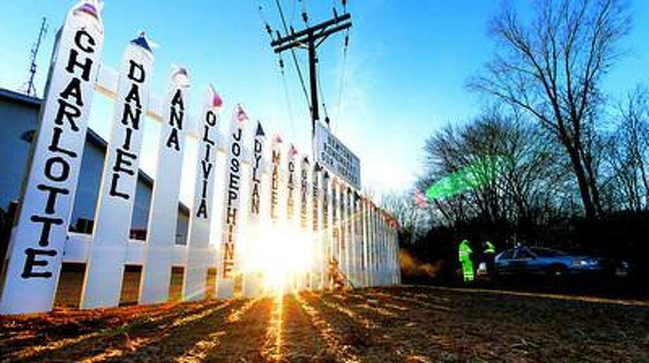 The memorial setup near the Sandy Hook firehouse, and the entrance road to Sandy Hook Elementary School continues to grow as seen here early Thursday morning December 20, 2012. The sun rises above the trees, illuminating parts of the memorial, as Connecticut State Troopers block of the entrance road to the Sandy Hook Elementary School. Tom Kelly IV/Staff photos / © 2012 Tom Kelly IV