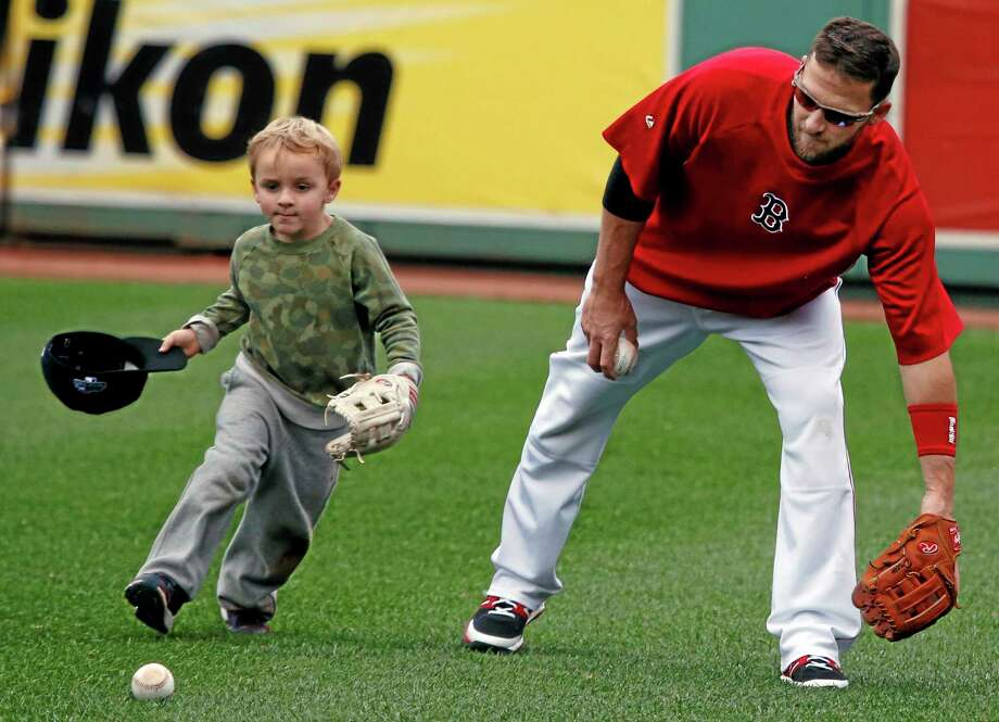 Boston Red Sox shortstop Stephen Drew plays with his son, Hank, during a team workout Thursday at Fenway Park in Boston in preparation for Game 1 of the ALCS on Saturday. Photo: Elise Amendola — The Associated Press  / AP
