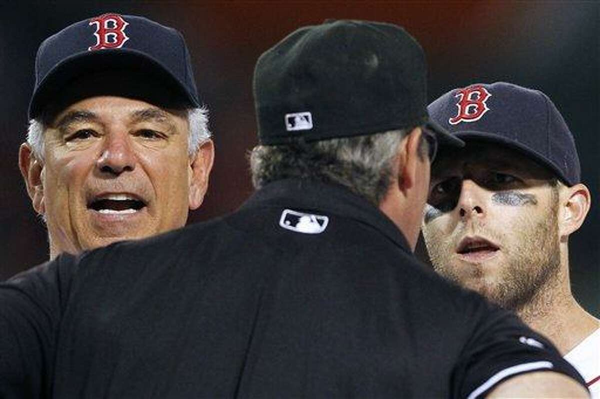 Boston Red Sox manager Bobby Valentine, left, and Boston's Dustin Pedroia, right, argue with first base umpire Paul Nauert in the ninth inning of a baseball game against the Texas Rangers in Boston, Tuesday, Aug. 7, 2012. Pedroia was ejected. The Rangers won 6-3. (AP Photo/Michael Dwyer)