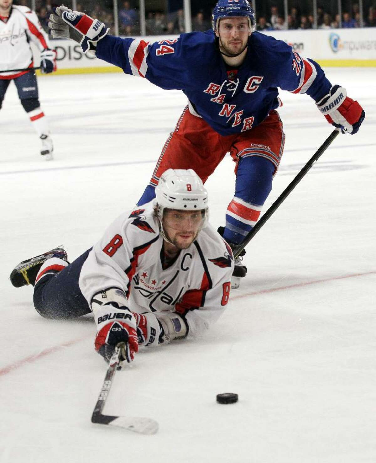 ASSOCIATED PRESS Washington Capitals' Alex Ovechkin (8) falls to the ice while fighting for control of the puck with New York Rangers' Ryan Callahan (24) during the third period of Game 1 of an NHL Stanley Cup playoff series Saturday in New York. The Rangers won the game 3-1.