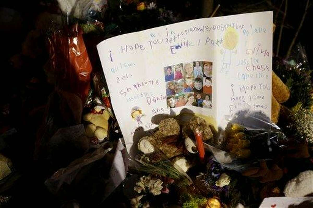 A poster written by children with the faces of some of the victims is among the many tributes at a memorial to the shooting victims in the Sandy Hook village of Newtown, Conn., Thursday, Dec. 20, 2012. Adam Lanza walked into Sandy Hook Elementary School in Newtown, Dec. 14, and opened fire, killing 26 people, including 20 children, before killing himself.(AP Photo/Seth Wenig)