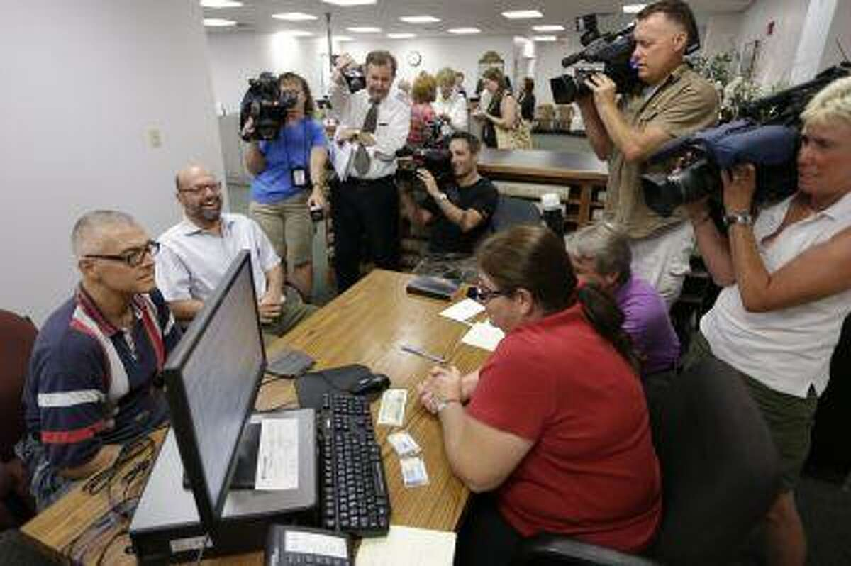 Marcus Saitschenko, left, and James Goldstein obtain a marriage license at a Montgomery County office despite a state law banning such unions, Wednesday, July 24, 2013, in Norristown, Pa.