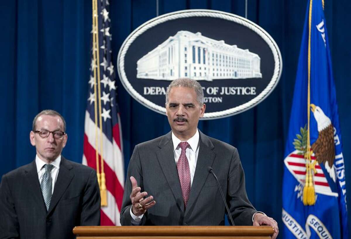 Attorney General Eric Holder speaks during a news conference at the Justice Department in Washington, Wednesday, Dec. 19, 2012, during an announcement that the international investment bank UBS Securities Japan Co. Ltd., will pay more than $1.5 billion in penalties in three nations to resolve charges of trying to manipulate an interest rate used as a benchmark in global banking transactions. Holder says UBS Securities Japan Co. Ltd., will plead guilty to felony wire fraud and admit to attempting to manipulate the London Interbank Offered Rate. Two former UBS senior traders will be charged with conspiracy, including one also charged with wire fraud in New York federal court. (AP Photo/Jose Luis Magana)