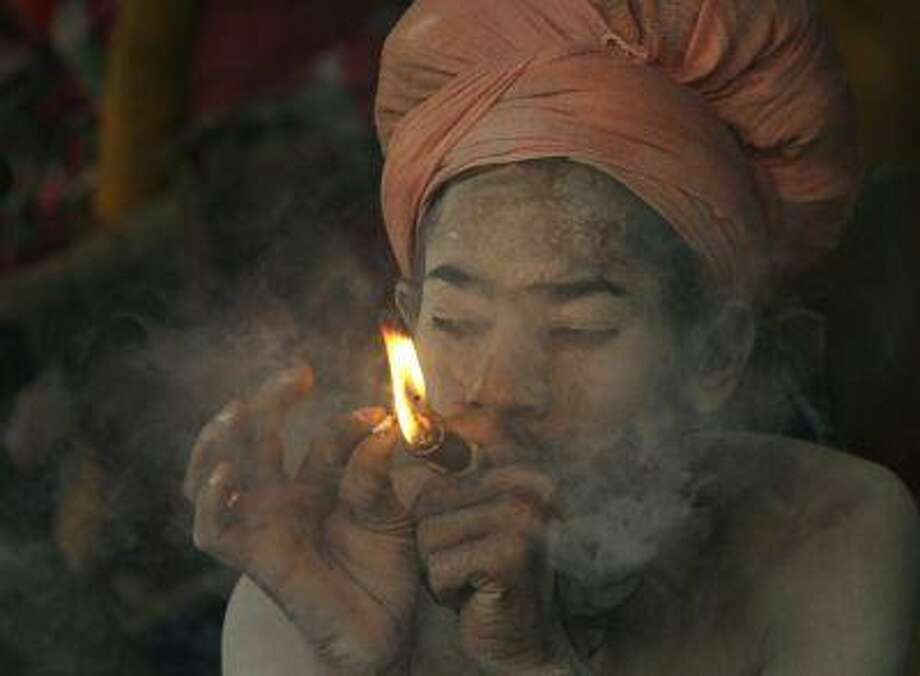 In this March 10 photo, an Indian naked Hindu holy man smokes marijuana before the Mahashivratri procession in Junagadh, in the western Indian state of Gujarat, India. Photo: ASSOCIATED PRESS / AP2013