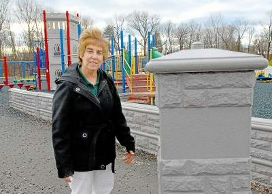 Catherine Avalone/The Middletown Press Cromwell Park & Recreation Director, Sue Schein stands alongside one of two towers at the entrance to Jensen's Playground at Pierson Park. The other tower was stolen as well as a other sections of the 13 year old playscape.