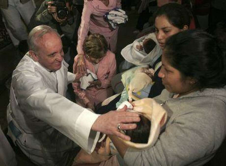 In this March 21 2011 photo, Argentina's Cardinal Jorge Mario Bergoglio touches a baby after a Mass in Buenos Aires, Argentina. Latin Americans reacted with joy on Wednesday at news that Bergoglio has become the first pope ever from the Americas and the first from outside Europe in more than a millennium. Photo: ASSOCIATED PRESS / AP2011