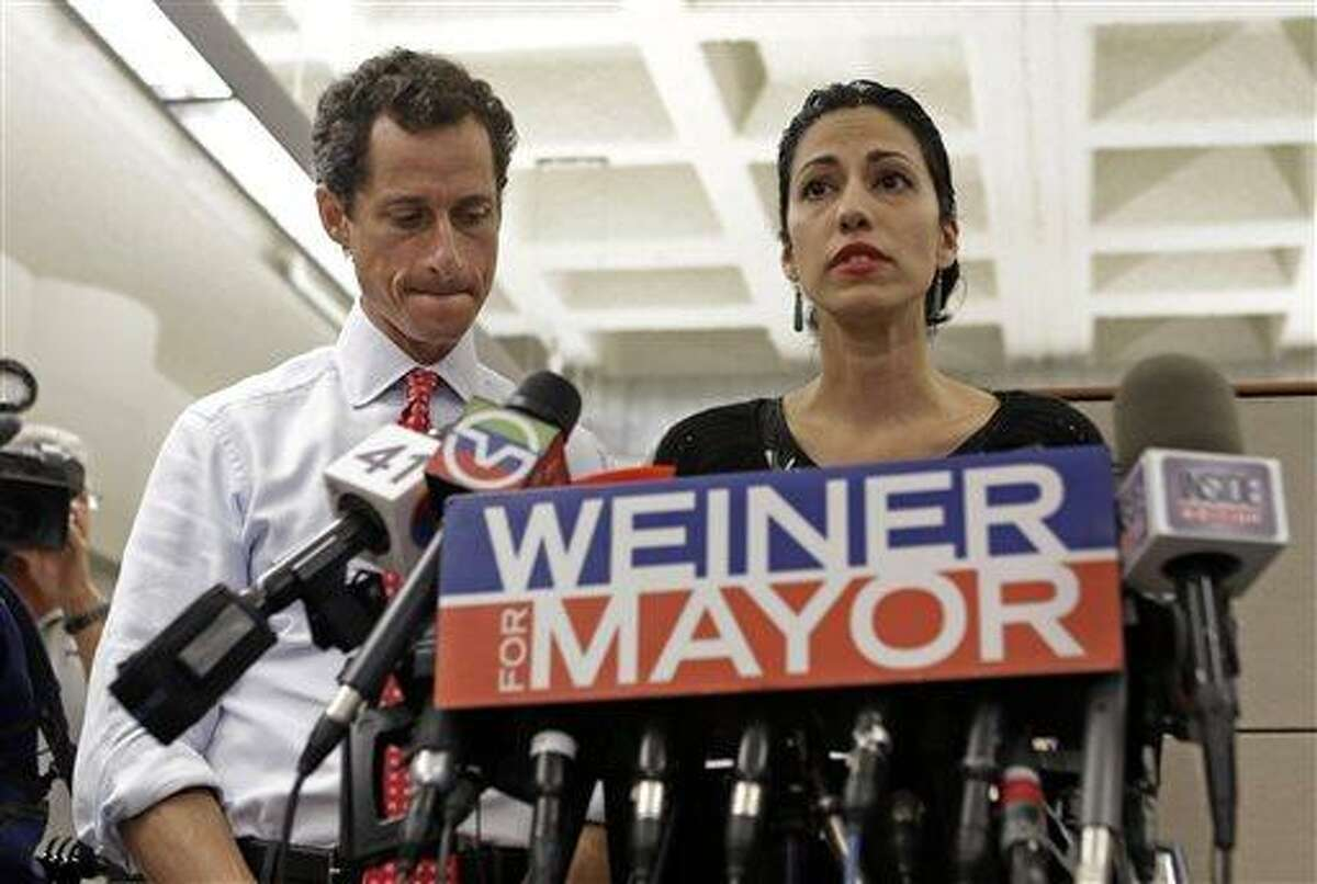 New York mayoral candidate Anthony Weiner, left, listens as his wife, Huma Abedin, speaks during a news conference at the Gay Men's Health Crisis headquarters, Tuesday, July 23, 2013, in New York. The former congressman says he's not dropping out of the New York City mayoral race in light of newly revealed explicit online correspondence with a young woman. (AP Photo/Kathy Willens)