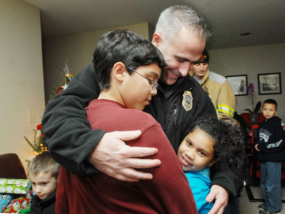 Catherine Avalone/The Middletown PressMiddletown Police Chief Bill McKenna gets a hug from children of a family who received gifts as part of the Adopt-A-Family