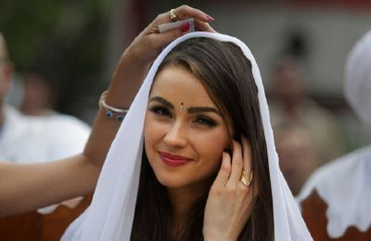 In this, Sept. 30, 2013 file photo, Miss Universe Olivia Culpo, watches a performance by inmates as designer Sanjana Jon, adjusts her veil during a visit to the Tihar Jail in New Delhi, India. (AP Photo/Tsering Topgyal, file)