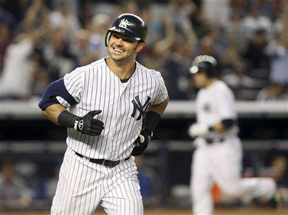 New York Yankees' Nick Swisher smiles while running the bases after hitting a grand slam during the third inning of the baseball game against the Texas Rangers Monday, Aug. 13, 2012 at Yankee Stadium in New York.  (AP Photo/Seth Wenig) Photo: ASSOCIATED PRESS / AP2012