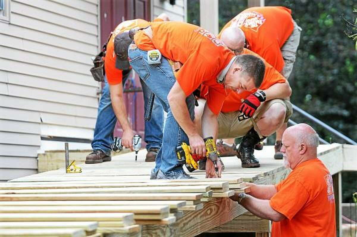 Curtis Gaudet, center and Ed Boice, at right, 2 volunteers of the 14-member Team Depot, Home Depot's associate-led volunteer force construct a handicapped accessible ramp at Fellowship Hall at United Churches of Durham Thursday morning. In the background, Jonathan Roy, Jim Miceli and Mike Glogowski attach decking to the ramp.
