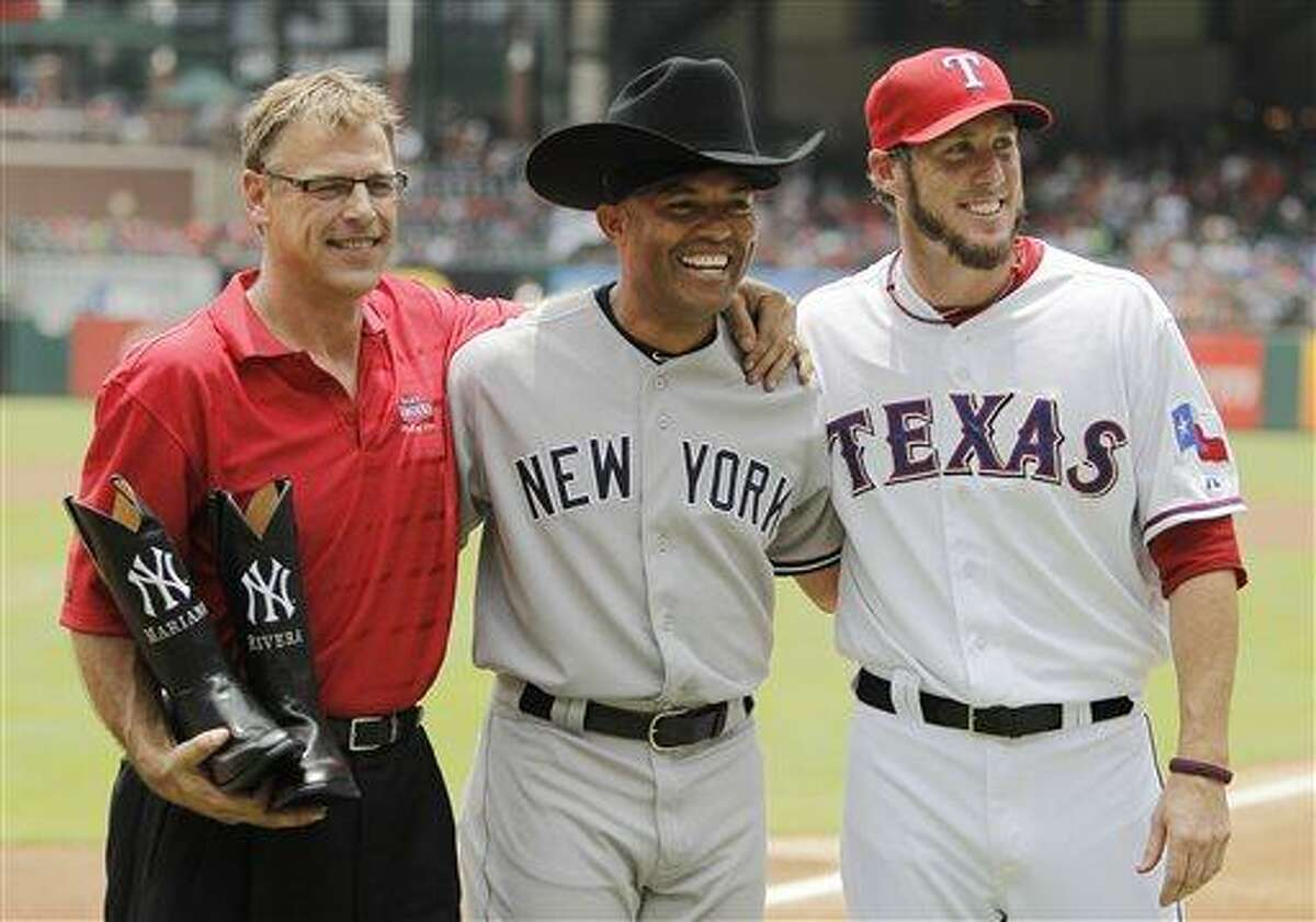 Former Texas Rangers closer John Wetteland, left, and Rangers relief pitcher Joe Nathan, right, pose for a photo with New York Yankees relief pitcher Mariano Rivera, center, after presenting him with cowboy boots and hat before the start of the first inning of a baseball game in Arlington, Texas, Thursday, July 25, 2013. (AP Photo/Brandon Wade)