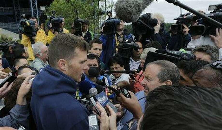 New England Patriots quarterback Tom Brady talks with reporters following a team NFL football practice in Foxborough, Mass., Thursday, July 25, 2013.(AP Photo/Charles Krupa) Photo: AP / AP