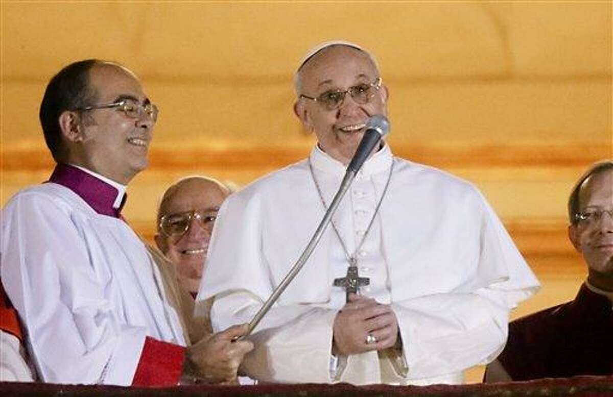 Pope Francis speaks from the central balcony of St. Peter's Basilica at the Vatican, Wednesday, March 13, 2013. Cardinal Jorge Bergoglio who chose the name of Francis, is the 266th pontiff of the Roman Catholic Church. (AP Photo/Gregorio Borgia)