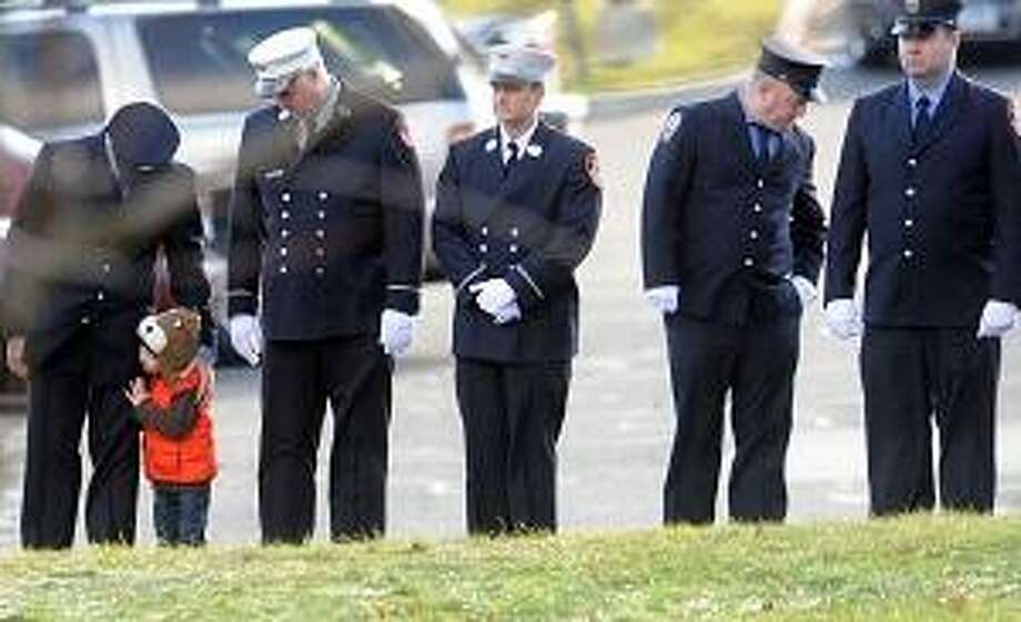 A firefighter with a young boy stands in line with other Connecticut firefighters from around the state as an honor guard during the funeral for David Barden , 7, of  at the St. Rose of Lima Roman Catholic Church in Newton, Conn.  Wednesday, December 19, 2012, who was killed by a gunman that also claimed the lives of 6 adults and 19 other children at the Sandy Hook Elementary School shooting Friday, December 14, 2012.   Photo by Peter Hvizdak / New Haven Register Photo: New Haven Register / ©Peter Hvizdak /  New Haven Register