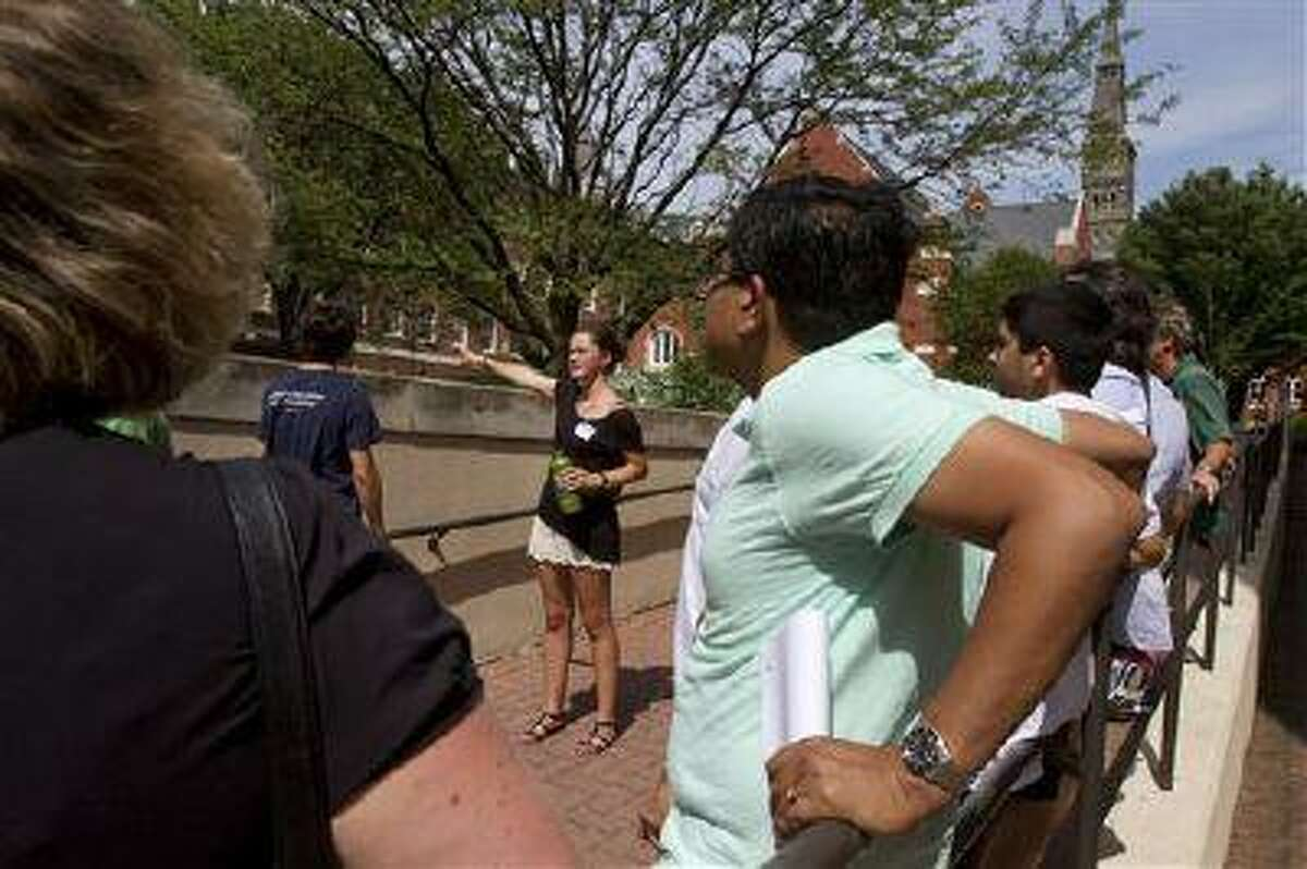 FILE - Prospective students and their parents tour Georgetown University's campus in Washington, in this Wednesday, July 10, 2013, file photo. Grants and scholarships are taking a leading role in paying college bills, surpassing the traditional role parents long have played in helping foot the bills, according to a report from loan giant Sallie Mae. (AP Photo/Jacquelyn Martin, File)