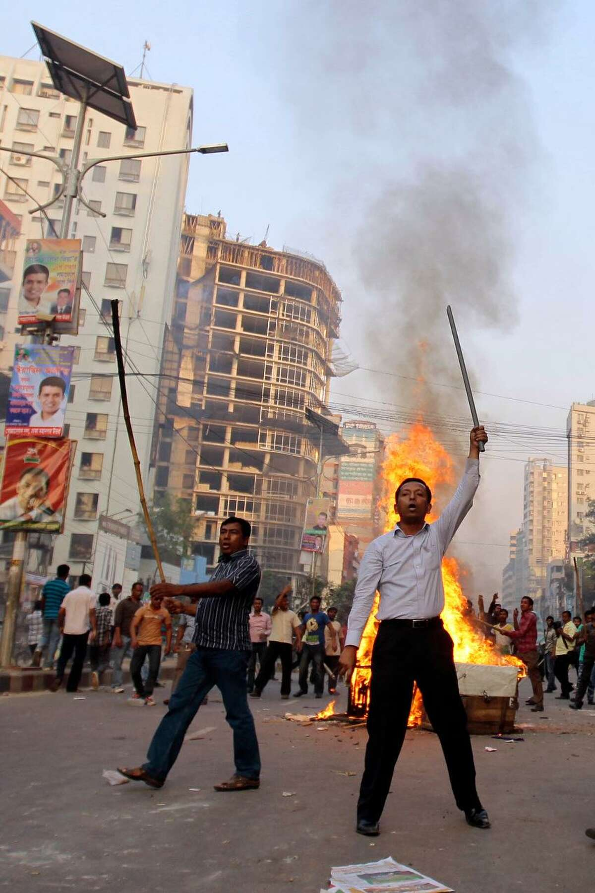 Bangladeshís opposition activists shout slogans after they burn a street vendor's cart as they clash with police during their protest in Dhaka, Bangladesh, Monday, March 11, 2013. The protest was called by an alliance of 18 parties to denounce trials of several opposition politicians accused of mass killings and atrocities during Bangladesh's 1971 independence war against Pakistan. (AP Photo/A.M. Ahad)