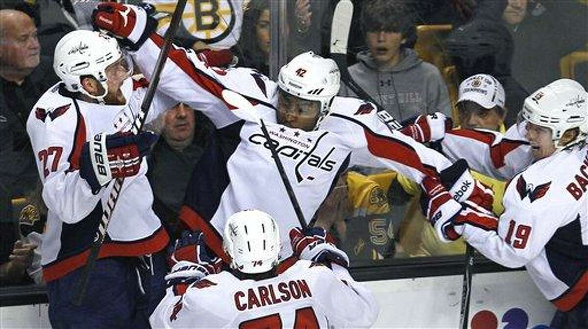 Washington Capitals right wing Joel Ward, center, is congratulated by teammates after his game-winning goal against the Boston Bruins during overtime of Game 7 of an NHL hockey Stanley Cup first-round playoff series in Boston, Wednesday, April 25, 2012. The Capitals won 2-1. From left with Ward are Karl Alzner, John Carlson and Nicklas Backstrom. (AP Photo/Charles Krupa)