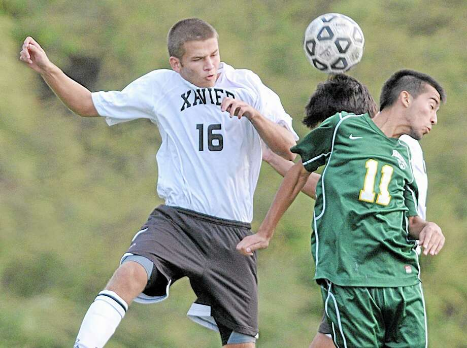 Xavier's Brendan Cutuli (16) and Brett Mooney (21) (in back) battle Hamden's Martin Nunez Wednesday afternoon at TD Bank Oakwood Soccer Park in Portland. The undefeated Falcons won, 3-0. Photo: Catherine Avalone — The Middletown Press  / TheMiddletownPress