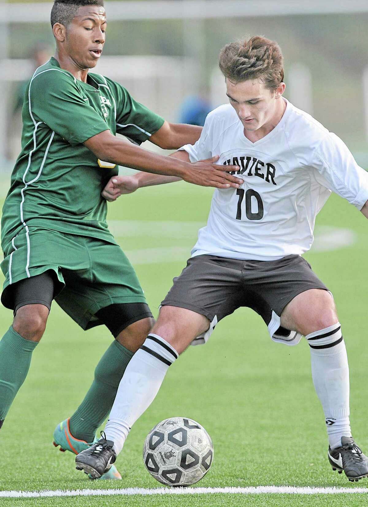 Xavier forward Brendan Butler is challenged by Hamden's Gary Stanley Wednesday afternoon at TD Bank Oakwood Soccer Park in Portland. The undefeated Falcons won, 3-0.