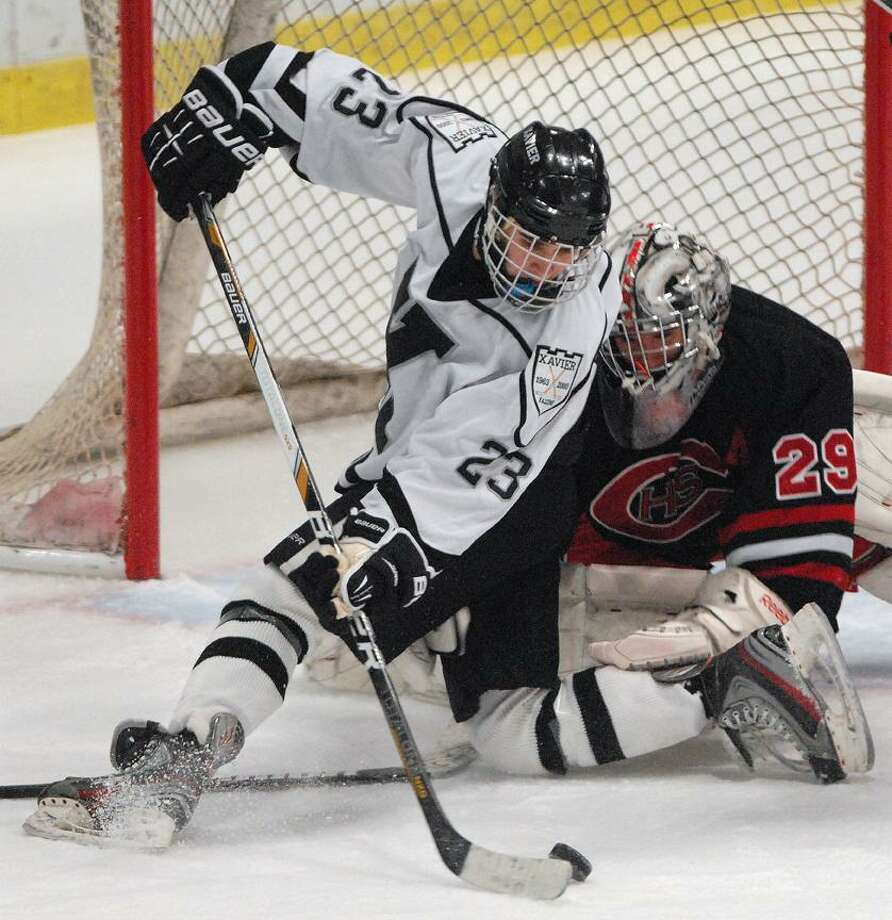 Catherine Avalone/The Middletown PressXavier senior forward Ryan McLellan battles Cheshire senior goalie Scott Romano Wednesday night at the Spurrier-Snyder Rink at Freeman Athletic Center at Wesleyan University in Middletown. The Xavier Falcons defeated the Cheshire Rams 3-1.