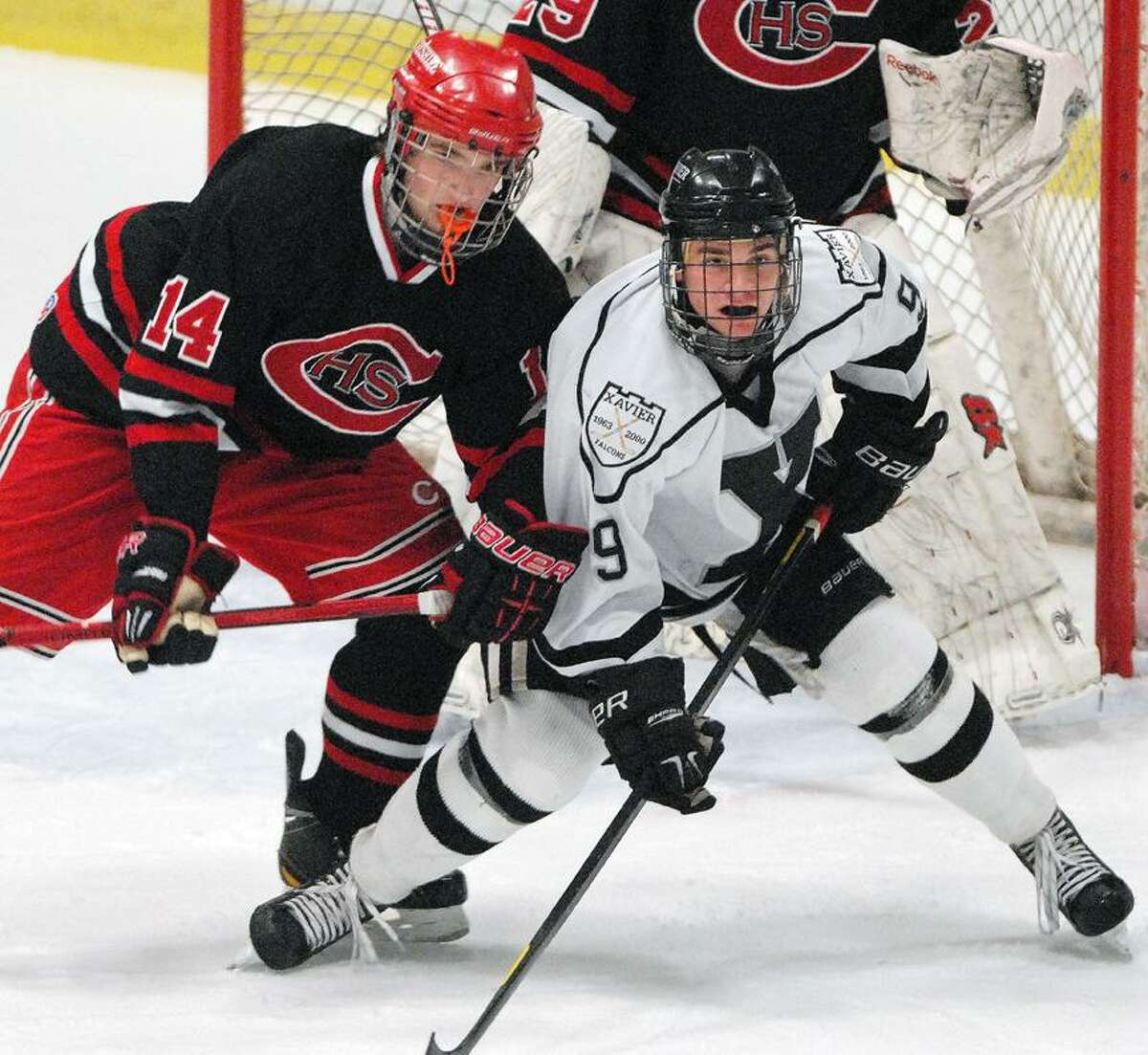 Catherine Avalone/The Middletown PressXavier junior defender John Burkinshaw battles Cheshire junior Dan Purslow Wednesday night at goal at the Wesleyan's Spurrier-Snyder Rink at Freeman Athletic Center in Middletown. The Xavier Falcons defeated the Cheshire Rams 3-1.